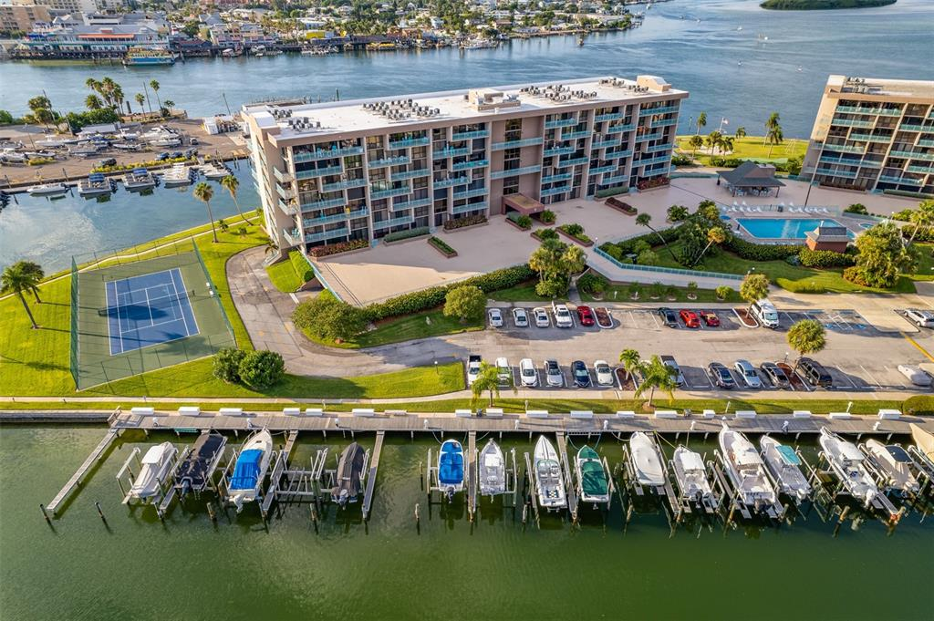 Welcome to the resort style gated complex of Key Capri, perfectly situated in the heart of Treasure Island on its own 6+ acre island!  This END/CORNER 2 bedroom 2 bath waterfront condominium is a must see, offering numerous upgrades and beautiful SW views of the marina and the Gulf of Mexico. The open kitchen features new quartz counters, and a large single undermount stainless steel sink and faucet.  The dining room opens to the living room with sliding doors to an expansive balcony to enjoy the amazing sunsets as well as sun and moon rises. It is a desirable split bedroom plan with the owners suite and its floor to ceiling windows that face Southwest and overlook the Gulf and marina with en suite bath with a walk-in closet as well as 3 additional closets for added storage.  Other key updates include the new HVAC in Nov. 2020, shutters for the south facing sliding doors and windows and stylish laminate flooring in the living room and bedrooms.  There is a covered parking space under the building with a sizable storage shed included. Key Capri condos are a waterfront residential resort community overlooking John's Pass. The gated complex affords a resort lifestyle with its many amenities that include: Geo-thermally heated and cooled swimming pool and spa; on site marina and first come first serve rental slips that are one of the best deals in the area with quick access to the Gulf of Mexico; fishing dock; kayak and paddle board storage rental spaces that include use of launch; waterfront Tiki hut, barbecue grills with picnic area, putting green and tennis / pickleball and shuffleboard courts; fitness center with saunas and lockers; half mile walking path around the property; under building parking and storage; car wash station; social room with full kitchen, recreation room with billiards and ping pong tables; library; craft room; workshop; and on-site management office.  Sorry, No Dogs Allowed.  Make your appointment to view today!