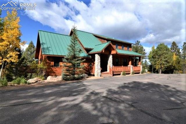 Beautifully Furnished/Turnkey Custom Home ~ Guest Cabin w/ 3BR/3 Baths, ~ 6-Stall Barn ~ 3-Car Detached Garage w/ Tool Room ~ Western Mountain Views ~ (2) Ponds, 1200+/- Ft Twin Creek ~ Aspens & Pine ~ Multiple Outdoor Entertainment Areas: Covered Porch, Wrap-Around Deck w/ Hot Tub, Picnic Deck w/ Gas Grill & Built-in Benches, Walk-out Patio ~ Barn w/ electric, water, 8' high drive- thru doors ~ 5+/- Acres Fenced w/ (2) Paddocks ~ Paved Driveway ~ Entry Gate ~ Quiet, Private Location  Close to Divide & Woodland Park