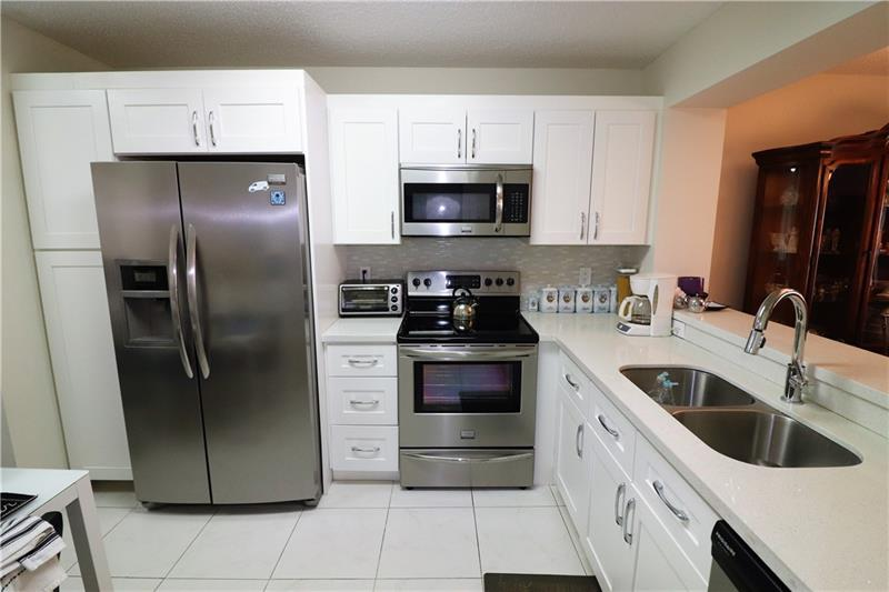 Spectacular Condo feels like a lake home with stunning lake and fountain views. Pull up to your front door and walk into to your new lake home on the 1st floor at Weldon, Kings Point. Amazing Opportunity for this upgraded 2 bed 2 bath Rose Model condo in the meticulously maintained Weldon Section. Condo features off-white tile throughout with wood laminate in bedrooms. The Remodeled Kitchen includes white wood cabinets with chrome handles, white quartz countertops, stainless appliances and washer/dryer. This open kitchen design with pass-through creates a bright contemporary feel with lots of light from its north/south exposure. The condo is in spotless move-in condition and priced to sell. Enjoy the 60,000sq.ft clubhouse with endless activity's and services.!Assoc.requires one owner 55+