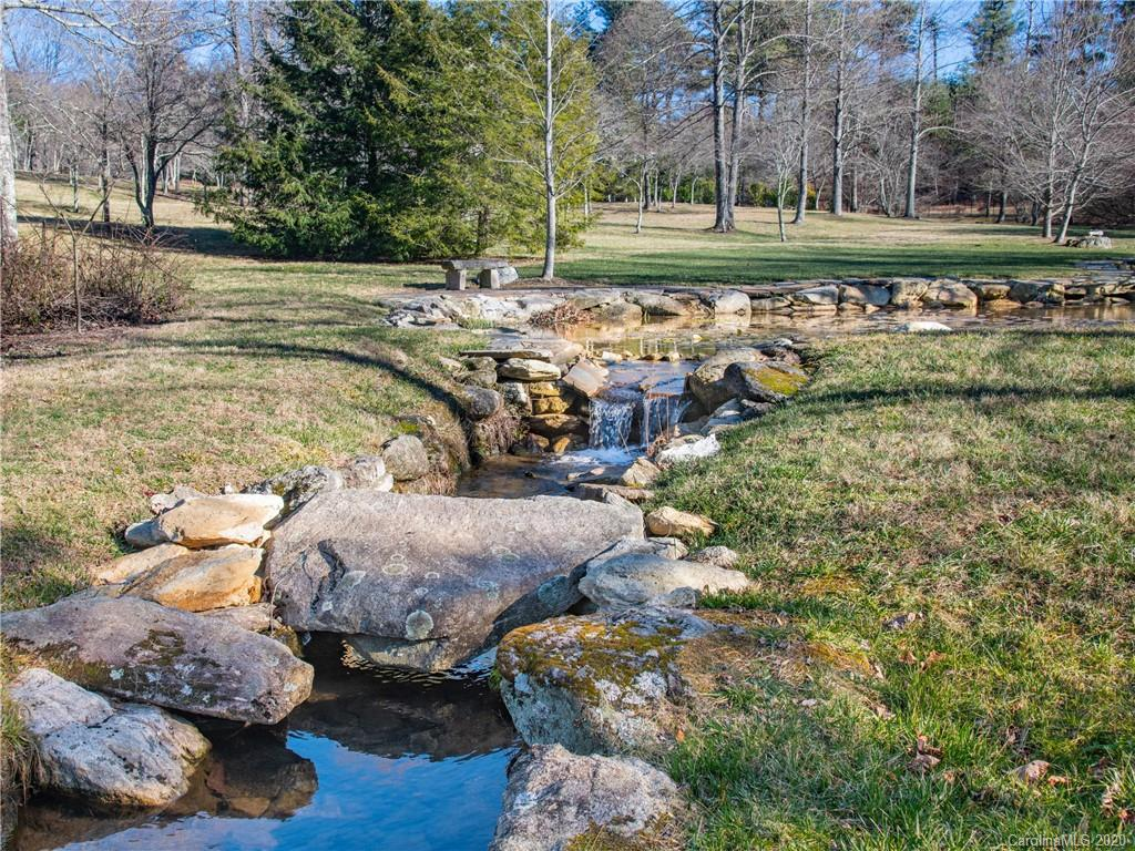 RARE FIND / PRIME LOCATION! Premier grand estate size lot located in prestigious Kenmure, a gated golf course community in Flat Rock, NC. This absolutely gorgeous 5 plus acre lot is situated in one of the most desirable sections of Kenmure. This mostly level lot boasts a beautiful manicured pastoral setting with mature trees and cascading stream (3 streams meander together forming 4 ponds-one being a lily pond) featuring professionally landscaped rock borders, boulders and rock benches.  Ideal property for a one level home or estate size home with a level entry and yard. Underground utilities, city water and natural gas available. Multiple 4 BR (expired) septic permits. Amenities include golf course, tennis and pickleball courts, indoor and outdoor pools, fitness center and antebellum clubhouse. Membership in the club is optional. Very convenient to entry gate and clubhouse. Additional acreage available. Don't miss this rare opportunity to own this one-of-a-kind property.