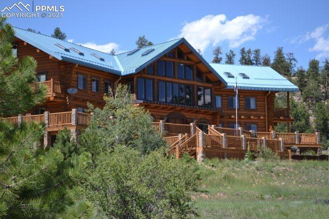 Grand 2-Story Log Lodge w/ snow-capped Pikes Peak Views ~ Impressive Great Room w/ 30+ft Ceilings, Wood Floors &  Fireplace, (4) Bedrooms-all w/ Adjoining Private Baths ~ Gourmet Kitchen ~ Separate Dining ~ (2) Office Areas ~ Large Multi-Level, Wrap-Around Deck Perfect for Entertaining ~ Commercial Water Well ~ Gently Rolling Terrain  ~ High Point w/ 360 Views of Sangre de Cristo's, Pikes Peak, Wright's Reservoir, Mueller State Park, Slater Creek & Fourmile Valley ~ Towering Rock Bluffs