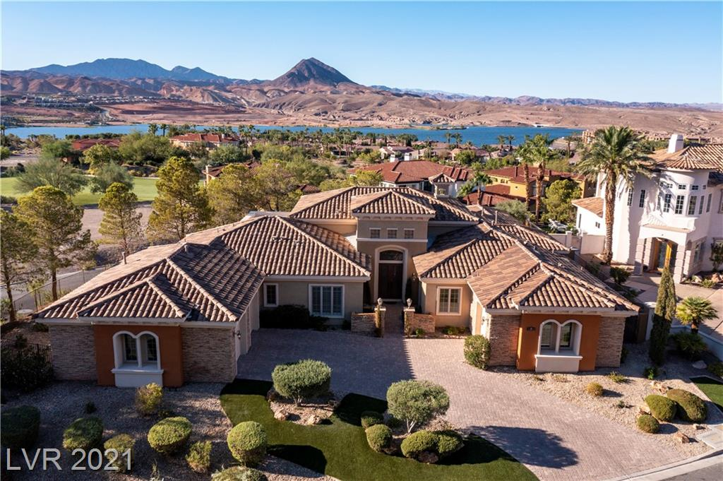 Spacious single-story home with open floor plan in the guard gated community of SouthShore at Lake Las Vegas. The great room area includes high ceilings; a long breakfast bar overlooking an expansive kitchen with custom cabinetry and a large walk-in pantry; a circular dining area; fireplace; and wet bar. The home is perched on a hill with plenty of backyard patio space for entertaining and enjoying the pool. The owner's suite encompasses one wing of the house with a large bedroom, sitting area, bath and two walk in closets.  The opposite wing has the guest bedrooms and laundry. The guest quarters are attached to the house, but is accessed from the exterior and has its own garage. Mins from restaurants, shopping, hospitals, outdoor activities and only about 30mins from the Las Vegas strip.