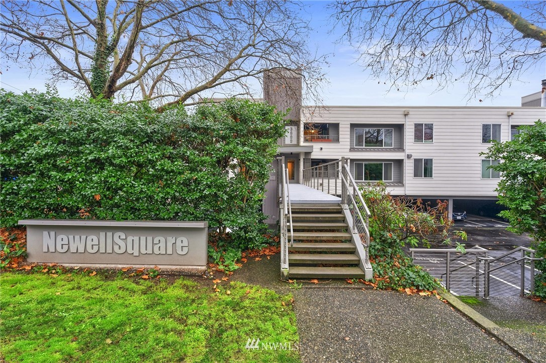 Beautiful tree lined street in Queen Anne showcases this renovated Roger Newell designed building. Industrial exterior finishes, newer roof & windows, gray steel siding, shared roof top deck perfect for stargazing, secure lobby access, basement storage & bike room! Unit features soaring ceilings & a wall of windows offering endless natural lighting. A rare 2-story condo w/open kitchen, dining and living room + pantry & extra storage. Loft style bedroom up w/full bath & in unit laundry. Hallway access from main living area AND loft! Assigned COVERED parking & furry friends allowed! Nestled with a Western view overlooking the Lake Washington Ship Canal / Ballard Fishermen's Terminal & Magnolia it is sure to please! Don't wait!