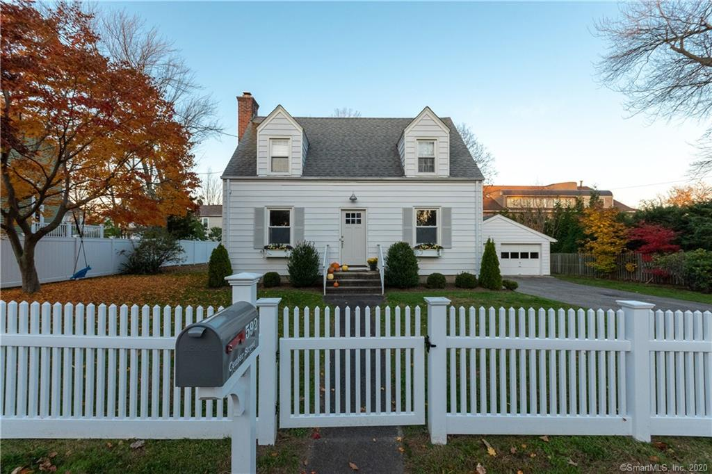 """All fixed up & ready to transfer, this sweet Colonial Cape has been lovingly fixed up by a young couple during their first 5 years of marriage!! Set on an oversized village lot of .26 acre, with a white picket fence added last year & window boxes to further adorn the landscape there is also the plus of a 2 car garage!! As you enter through a handsome front door a traditional layout greets you with sparkling hardwood floors. The classic Living Room features a wood burning fireplace with handsome mantel & surround, centered on the outside wall. Newish windows let an abundance of natural light stream throughout. The Family Room/Den is adjacent & has a full bath with large stall shower. The traditional Dining Room is on the other side of the entrance, with built-in corner cabinet. The owners have opened one wall from the adjacent new kitchen allowing for an open welcoming hospitable feeling! The kitchen has its own side door entrance from the yard & driveway areas, just steps from the large garage. The appliances include a natural gas stove top range/oven, large double door refrigerator/freezer, microwave, dishwasher & the so very clean look of quartz counter tops! From the kitchen a flight of stairs goes to the full basement with steps out to the patio & fenced yard. The second floor has an ample sized Master Bedroom with 3 closets, stairs up to a floored attic; 2 additional bedrooms & a Hall Bathroom with tub/shower. It truly is a happy house to call """"home sweet home""""!!"""