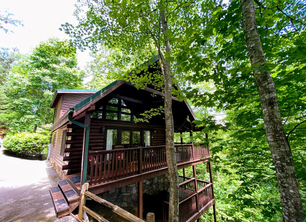 """GORGEOUS, TURNKEY, 3 BEDROOM, 3 BATH CABIN IN THE HEART OF GATLINBURG WITH SEASONAL MOUNTAIN VIEWS!  """"Gray Fox Den"""" has done awesome on the rental program with VRBO, has 84 5 star reviews and is currently booked solid for the remaining part of the year and part of 2022!  Both private and serene, this mountain home is adorned with an abundance of covered porch space where you can enjoy the peacefulness nature provides. Step inside and you will find lovely dcor, soaring cathedral ceilings, gleaming hardwood floors, stack stone fireplace, floor to ceiling windows and ample space for guests to kick back and relax.  Each floor offers the convenience of a private bedroom and bathroom, all beautifully decorated.  Downstairs, you will find an amazing media room with a large screen tv and comfortable theater style seating.  The community offers an alluring outdoor pool space to cool off in the heat of the summer months while your private hot tub is waiting to soak in after a day of sight seeing. This incredible cabin offers both convenience and amenities and will not last long! Make an appointment today!"""