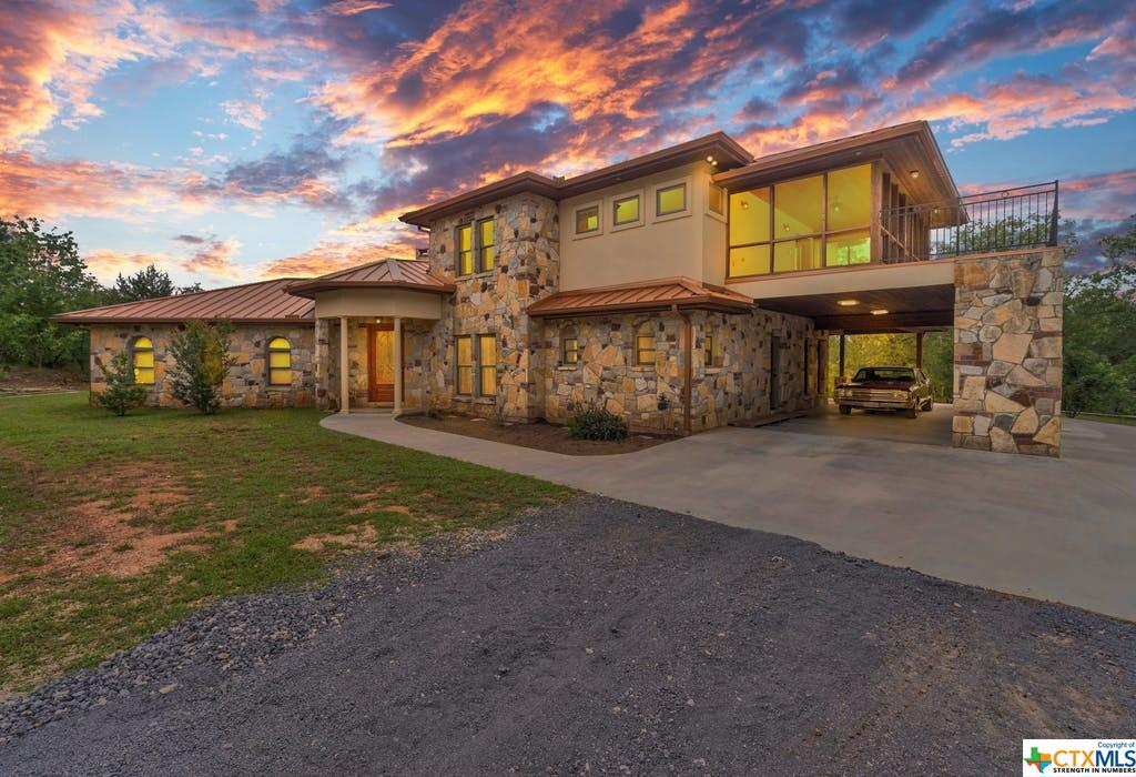 Gorgeous, one of a kind, custom built home located on 29.56 acres! Enjoy the cool breezes, peace and tranquility from the beautiful patio and balcony! The acreage has beautiful, mature trees and a wet weather creek!  The beautiful, hill country style rock home has two masters, one upstairs and one on first floor! Gourmet kitchen with beautiful granite! Large kitchen island! Sub zero refrigerator, gourmet stove-gas! The kitchen and dining room are open to the spacious family room. Beautiful fireplace! Gorgeous cypress wood throughout the home! Spacious office on first floor. The utility room is large and has a sink, icemaker and full bath! This is a must see! No restrictions. Hunting allowed. Located just an hour from Austin and San Antonio!