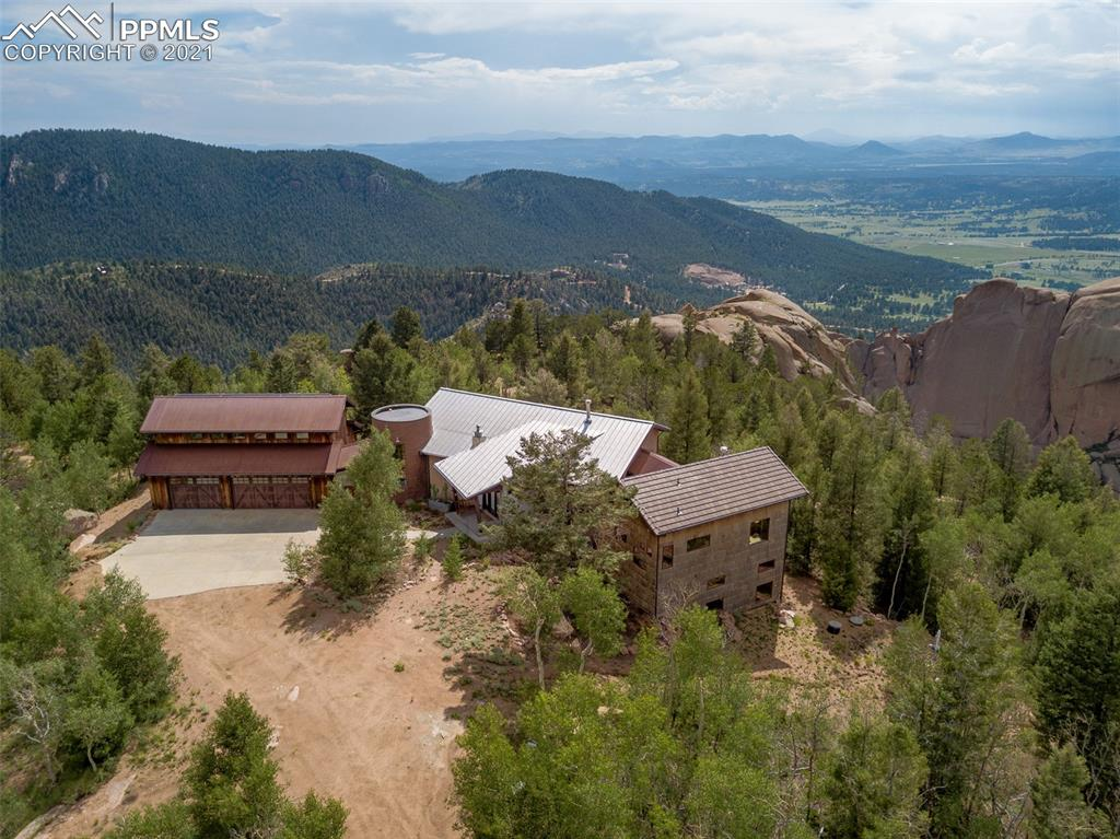 This one of a kind mid-century modern, meets rustic majestic mountain home, with a hint of Luxury, sits on the most breathtaking 35 acres you could ever imagine. A true 'take your breath away' experience right down to the last detail.  Marvel at the modern wood burning fire place that spins all the way around so you can enjoy a rotating 360 degree view from every vantage point in the home. The Gourmet Chef's Kitchen with a brick oven,  breakfast bar, prep area for the 'sous chef' and high end stainless appliances will make you want to create a Michelin worthy meal every night. Architectural design elements are abound in this home with the 'silo style' round library, locally sourced tree wall treatment, modern lighting and repurposed barn wood defining the garage exterior. The Master Retreat has its own gas fire place and full spa bathroom with soaking tub and a walk in shower so big you can bring a book and spend the day! The views from the Master can only be described as a 'Design Coup!' Downstairs you have even more room to play with a spacious family/rec room, full 'Drive in Movie' themed theatre room, an over sized bedroom, full bath and a Bunk Room that was envisioned to sleep over 10 people so you will never run short on space for visiting friends and family. The Bunk Room bath has a 3 fixture sink, bathroom closet, and shower w/ a private changing room. You may want to keep area this a secret so your guests don't become permanent residents! Plus, there are TWO, finished BONUS rooms over the 3 car garage that work perfectly as a home office, home school room, craft room or even as additional spare bedrooms when you have extra visitors!  This home is the perfect vacation home or full time family home. And I'm sure it is no surprise it comes complete with security system, 1/3 time solar panels and a home control system. Every window and deck showcases gorgeous views of rock formations, mountains, valleys and skyline. This is your Colorado 'Dream Come True' Home!