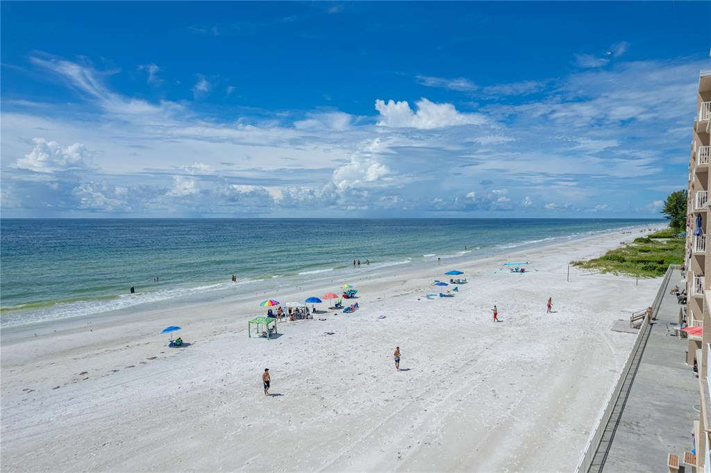 This beautiful 2-bedroom 2-bath corner unit condo offers stunning views of the Gulf of Mexico. The corner units in this building rarely go on the market and this offers you a great opportunity. This is also one of the larger units available in the building and has beach views from all windows including the bedrooms. As you walk in, you will see breathtaking views of the Gulf of Mexico. The owner has upgraded the windows and sliding doors with hurricane impact rated windows and doors. The bathrooms, kitchen and floors were upgraded as well. You have wood plank tile throughout which makes for easy cleaning from your days on the beach. The owner also added a washer and dryer for maximum convenience. The current owner rents the home out when he is not using it and takes advantage of our popular destination area and generates steady rental income (1 month minimum). He has great reviews and has regular returning renters that he is willing to share with the new owner. Having the tile throughout for easy clean for the beach, sleek granite countertops in the kitchen with an open floor plan for unobstructed views of the beautiful Gulf of Mexico plus the extra square footage and views from everywhere makes this an outstanding buy for a second home or investor. Enjoy Florida's year-round outdoor living and awesome sunset views from your private balcony or enjoy your views on the community deck located beachside. Amenities include the heated community pool for those that want a quick swim or a place to watch the family enjoy the pool. You can also enjoy time relaxing in the community clubhouse. You also have the use of a community hostess room across the hall from the home that features a full kitchen, two bathrooms, and lounge areas. You will find ample storage with a large closets in the owner's suite, extra closets in the hallways, and assigned, secure additional storage on the ground level for all those beach items. Assigned parking, secure key fob access to the community am