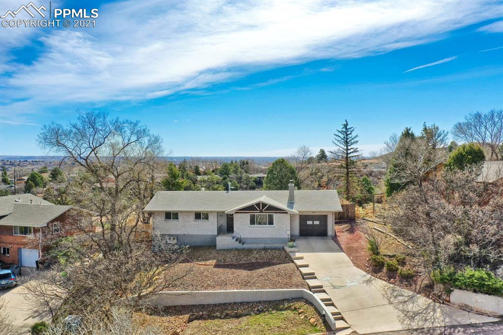 Perched on a hill with stunning unobstructed Pikes Peak Views from living room, dining room and master this home is a rare find in Manitou Springs.  Also not to be forgotten are the fabulous Garden the Gods and city lights views from a large, covered outdoor private outdoor patio. This tastefully remodeled home will be a delight to see with updated baths with new fixtures, vanities and tile floors, exterior paint, light fixtures and carpet. Enter to hardwood floors throughout the main floor, a great room with wood burning fireplace (plumbed as well for gas), and a formal dining room framed with Pikes Peak views. Sellers removed the wall by the stairs to open up the entire entrance area. The darling kitchen has ben modernized and walk out to beautiful fenced yard with large deck and paver patio plus an added bonus of outrageous view of city and Garden of the Gods. The main level offers master plus another bedroom currently used as an office and a remodels full bath. Walk down to the lower level with large recreation/theater type room, 2 additional bedrooms and a large laundry storage area with work bench and another updated bathroom. The lower level has updated carpet, paint and moldings. The home has central air and a radon system.  Close to schools, Manitou Springs shops and restaurants. Walk to the Cantina! Located in such a desirable location in the Crystal Hills area, this home is a Manitou Springs treasure.