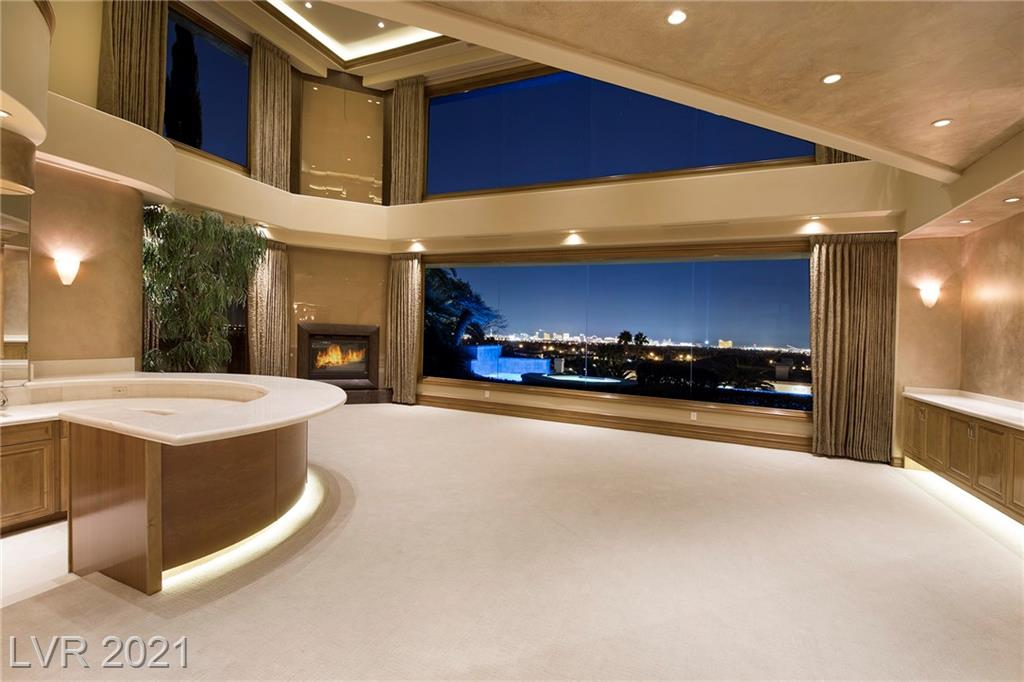LAS VEGAS STRIP & CITY VISTAS - Only the best in this exquisite custom estate with over 14,000 sq ft.  7 bedrooms, 11 baths, commercial elevator, 10 plus car garage w back up generator room.  Media Room, Office, Game Room. Over 3000 sq ft Master Suite overlooking the city.  Master Bath has it all with Steam & Sauna and posh dream closet. Laundry on each floor.  Basement complete with same luxury finishes, kitchenette, staff quarters, game room plus storage room.  Beige decor and  slab marble flooring.  Partially furnished. You can not duplicate this estate for less then ten million.  If you are looking for a large estate this home should be 'a must see' on your list.  You can always change the interior of a home but the panoramic views from this home can not be duplicated anywhere.  Ten minutes to the Strip. Located in posh landscaped guard gated community of Spanish Hills with tennis courts and park.   Formerly owned by our Las Vegas Star - Nicolas Cage.  Sunset showings available!