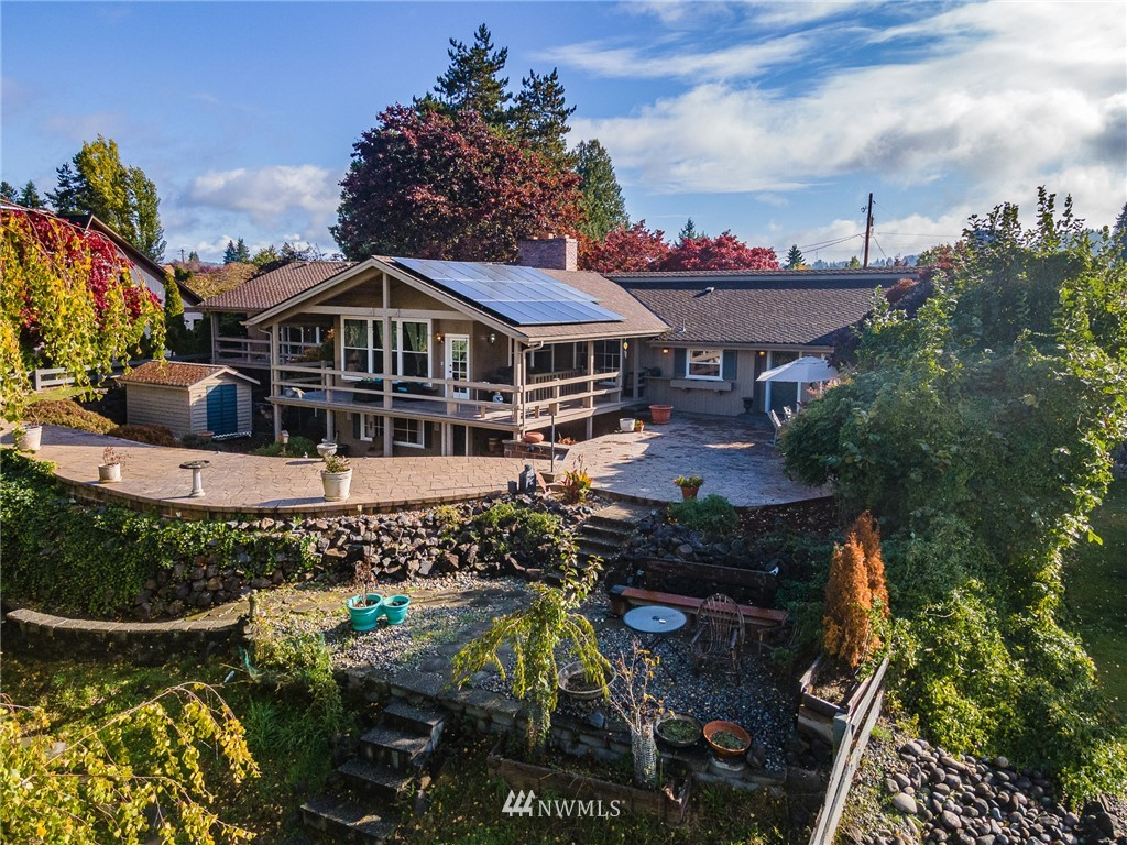 Gorgeous Pacific Northwest Craftsman Home w/ 112' of Lakefront Property! 5671 sqft, 4 BDs + 2 Bonus RMs, 3 Living RMs, 1 Full BA, 2 BA w/ Shower, & Renovated .5 BA in main hallway! ½ Circle Driveway, 2 Car Garage, Fully Finished Basement, & Workshop that leads outside. Enjoy the exposed wooden beams, balcony off the Master BD, open concept Kitchen & Living RM, formal Dining RM, elevated main Living RM + Wood Fireplace, sunken Living RM downstairs w/ Wood FP & adorable Loft above the garage! Relax in the backyard on the stamped concrete patio, the balcony, or the bottom floor. Concrete dock w/ firepit, protective retaining wall, shed, & dog run! $30k in Solar Panels, 50 yr Roof, New Storm Windows, 2 Heat Pumps, & 2 Zone Central Air w/ A/C!