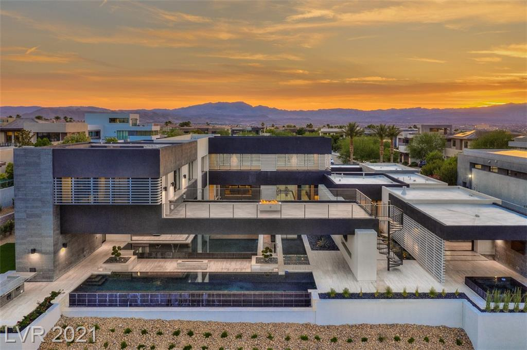 NEW, MODERN entertainer's paradise w/full Strip views! Never been lived in! Newly completed outdoor kitchen & landscaping at this Modern Marvel. One of a kind Blue Heron architectural style w/the perfect blend of indoor/outdoor living. This stunning home satisfies every craving! Features include a wine cellar, sky deck, exec. office, basement, courtyard, disappearing doors, outdoor pool bath, bridge/water entry, soaring ceilings & chic furnishings. Endless possibilities w/vacant lot next door that is included in offering. The concept renderings call for an additional 8 car garage (which would total 12 car) & approximately 1,200sf casita w/living space & 2 additional bedrooms. The views are world-class w/the golf course, mountains & famous Las Vegas Strip. Primary suite has a private patio, atrium & generous walk in closet. All bedrooms are ensuite. W/today's material price increases & 2 full lots included, you would be challenged to replicate this Modern Marvel at the offering price.