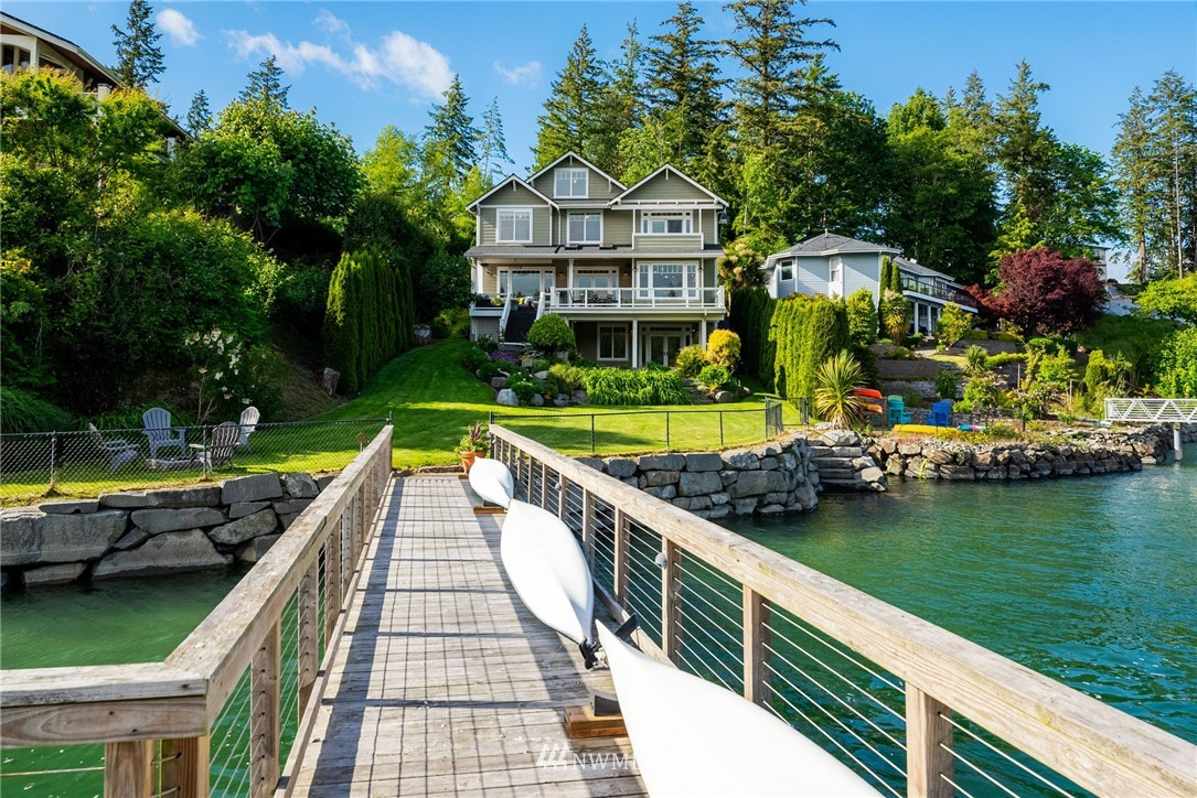 Cross the bridge and you've arrived at a little slice of island paradise! Welcome to this lovely custom built, south facing, low bank waterfront home on desirable Raft Island. 60 ft. of waterfront w/ a deep water dock (up to 32' overall.), bulkhead & stairs to the beach. Views from almost every room. What's for dinner? Clams & oysters from your private beach, cooked up in your gourmet kitchen, of course! The open concept main floor French doors lead to the relaxing deck, which offers amazing views and overlooks the gardens & grassy yard. There's two extra finished rooms & a full bath upstairs, and the family room downstairs has a mini kitchen, 3/4 bath, W/D hookup, outdoor shower & separate entrance. Come enjoy island life - it's the best!