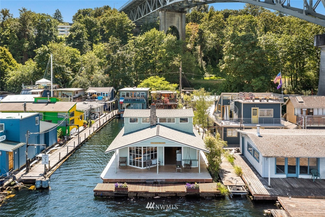 Available for the first time in decades, wide open views are just the beginning! This beautiful end of dock floating home has an incredible legacy!  Surrounded by water on three sides, this was the birthplace & original location of The Center For Wooden Boats.  Unanimously voted the honor of historical landmark status by the city & long admired as a jewel in our floating home community, this is a once in a lifetime opportunity. Larger scale Lake Union living than we are used to seeing on the water! It also has the most spectacular covered wrap around porch on the lake! The main level has a primary and extra bedroom, but don't miss the upper level w/ two more great spaces which can be used as one or two bedrooms. Boat moorage & easy parking.