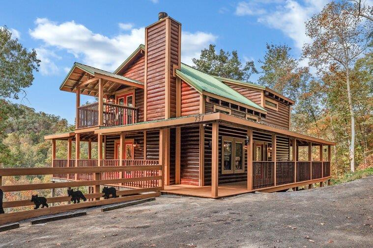 """""""Hold My Bear"""" is a MONEY MAKING cabin in a perfect location close to Pigeon Forge, Gatlinburg, and Wears Valley! Minutes from the Parkway! In its first full year with a new property management company, it grossed $88,000! Estimated to gross up to $100,000 in its 2nd year. Located on almost an acre, the cabin is nestled in the woods and makes for a private retreat!  A great floor plan with 3 large bedrooms and 3 bathrooms. One on each level! There are wrap-around decks that are surrounded by huge trees with a hot tub that is perfect for enjoying the views and the sounds of nature! On the main level, you will find a gas log fireplace in the living room, a fully stocked, cozy kitchen with brand new stainless steel appliances, and a king bedroom with an ensuite bathroom. Upstairs is another king bedroom with an ensuite bathroom and a loft with a pool table, tv, and bar seating. The basement features a theater room with a 75"""" flat screen tv to watch your favorite movie with friends and family, a queen sleeper sofa, dartboard, and access to the lower deck. Downstairs you will also find the 3rd bedroom with double queen beds and the 3rd bathroom. There is deck access from the lower level as well!"""