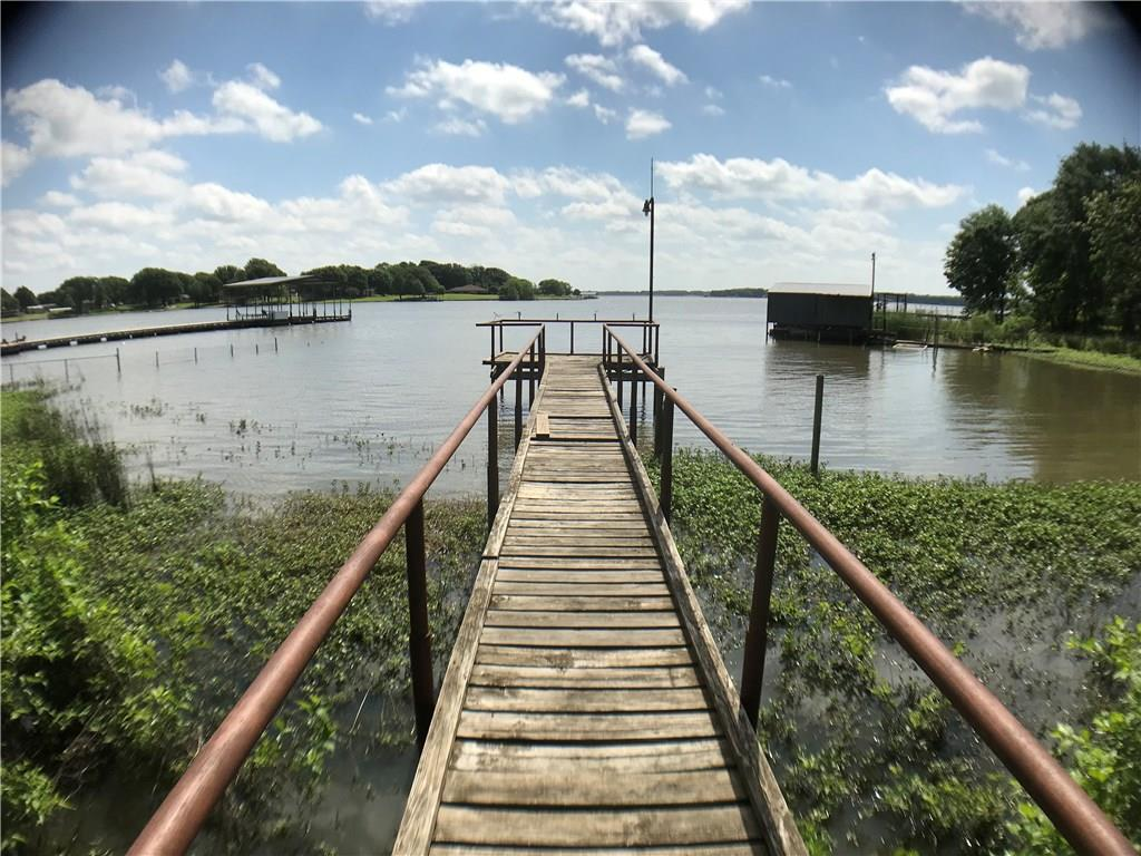 Lakefront Property situated on Lake Bonham.  HOME AND WORKSHOP HAS BRAND NEW ROOF REPLACED JULY 2018!  Great weekend getaway, homestead or corporate retreat set among towering oak and pine trees.  There is a 2nd building site with separate access off off Nunn Cir.  Enjoy your large wood deck overlooking a scenic, private pond as well as the private pier on the lake.  Very unique property with with gate access, quaint home with wood floors, 2 living areas, 3.5 baths, security system, fireplace, spiral staircase, plus much more!  There is a detached building with a 2 car garage and a 700 sqft bonus room with CHVAC, laundry room and bath. Land is annual lease with Bonham.  View web site for Rules and Regulations.