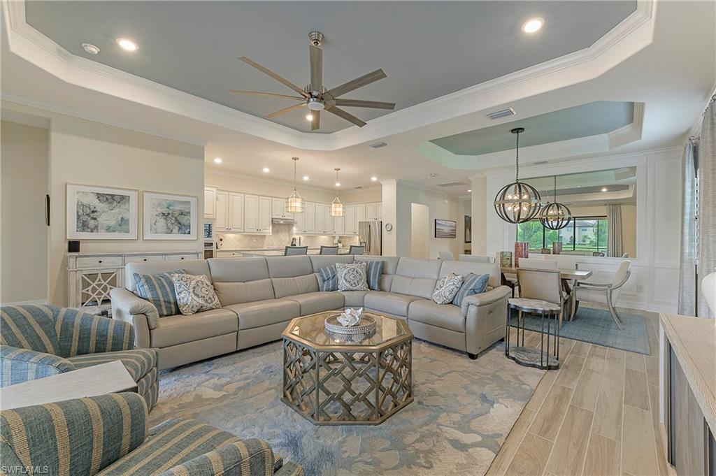 """The good life awaits you in this contemporary Lennar home in one of Southwest Florida's premier golf communities. Equipped with Alexa smart technology, this home is being offered turnkey with custom interior design by Baer's. The """"Maria"""" floor plan features 3 bedrooms + den and 3 baths, making it perfect for both family living and entertaining. The spacious kitchen with eat-at island features stainless appliances, quartz counter tops, tiled back splash, and an abundance of cabinet space. Upgrades abound throughout the home and include plank flooring, tray ceilings, plantation shutters, and custom mirror in dining area. Relax and enjoy beautiful golf course and lake views from the oversized screened lanai equipped with full outdoor kitchen and saltwater pool/spa. Located close to shopping, dining, entertainment and I-75, Bonita National offers a maintenance-free lifestyle with Golf Membership included in the purchase of your home! Don't miss out on the opportunity to experience resort-style living at its best in this move-in ready residence."""
