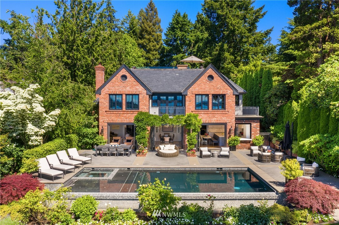 The Sophisticate on the Westside. A gated entry and stately brick exterior welcome you to this unparalleled west-facing estate on Hunts Point. Meticulously curated, sophisticated interiors open seamlessly to the infinity pool, terrace, and lawn to the shores of Lake Washington with Seattle skyline and Olympic Mountain views. Designed for entertaining, the 2016 home has timeless traditional lines with all the modern conveniences and amenities of luxury new construction, including an epicurean kitchen, a remarkable primary suite and exceptional style throughout. Every detail thoughtfully imagined and executed, from the home automation to the finishes to the outdoor living spaces lined by lush gardens. Private. Rare. Only on Hunts Point.