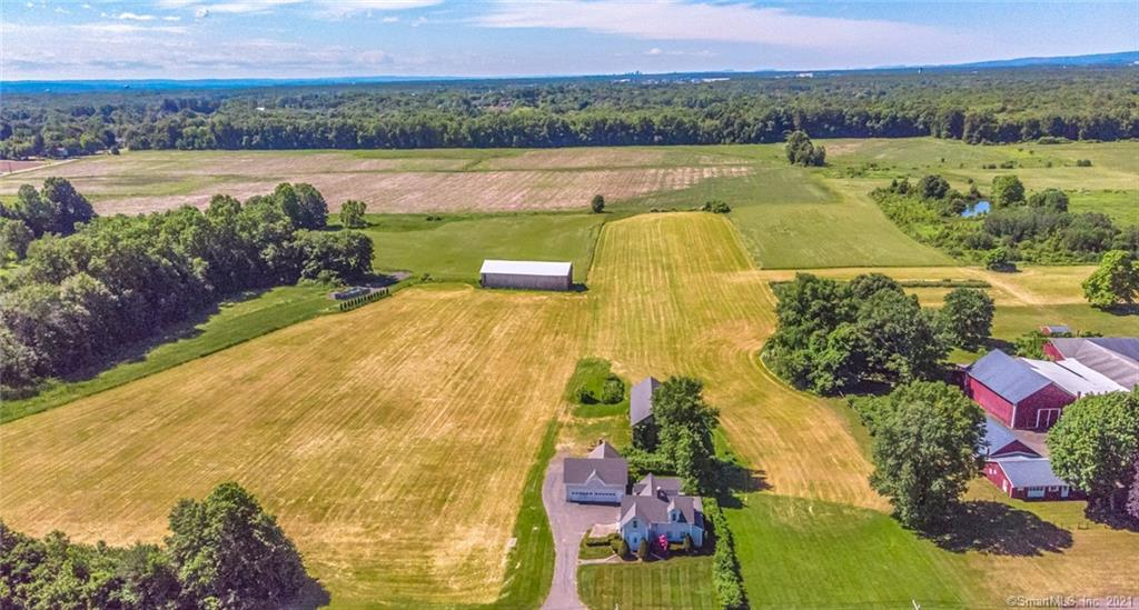 """Great opportunity to own a home on 11.9 acres of cleared, level, open-spaced land - near to the center of Suffield.  In addition to the home, the property has two full-size large barns and a detached oversized garage.  Approx 10.5 acres is currently used agriculturally for haying which offers the majority of the property a sizable farm tax exemption, hence the lower appraisal you may see online.  The home has 2 bedrooms on the first floor, with 2 full size baths and an updated kitchen area.  The 2nd floor has 1 bedroom, 1 full sized bath, an open living space and a full amenity kitchen area which has never been lived in.  This loft-style suite could be used as a master bedroom, an in-law residence or quite possibly as a rental unit.  The roof was replaced in 2014 and the home was extensively rehabbed and maintained by its current owner.  The land offers endless possibilities, including horses, farm, build your estate, agri-business or possible subdivide.""""  It is country living at it's best with an inter  national airport only 9 minutes away and 15-20 minutes to 2 major cities."""