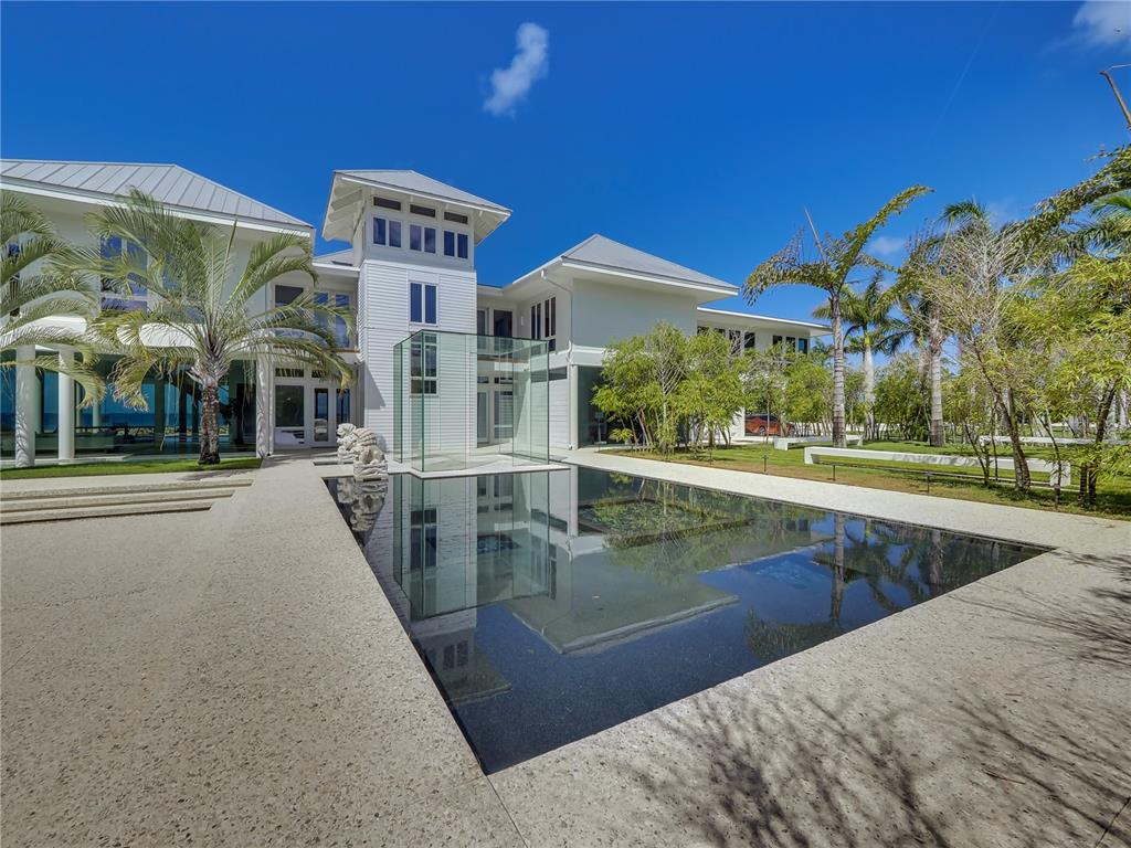 Live your best life now in this amazing, rarely available beachfront residence on Siesta Key. Tucked privately behind the gates of the exclusive Sanderling Club, this modern beachfront home better known as Aquadisia allows its owners to experience the best of its natural surroundings while being immersed in its luxurious offerings.  Aquadisia was thoughtfully designed by renowned architect, Guy Peterson in 1999.  Sited on 3.86 acres, the property is comprised of three parcels; the main house and two guest homes.  The 528 feet of private, pristine beachfront on The Gulf of Mexico undoubtedly makes this property one of the most significant beachfront properties available on Siesta Key.  The main house offers a warm, minimalistic modern design, with 6480 square feet of open and airy living space.  The artistically designed floor plan commands attention with pavilion-style wood ceilings and uninterrupted floor-to-ceiling windows that immediately reveal panoramic views of The Gulf.   The living room opens to the dining room and kitchen.  Immediately outside these areas  is an expansive 4,000 square foot deck that allows for relaxing, entertaining and endless viewing of the beach and Gulf.  The owner's suite includes a sitting area, en suite bathroom with walk-in shower and freestanding circular tub with the spigot in the ceiling.  The owner's oversized walk-in closet adorns a Swarovski crystal chandelier and plentiful built-in storage.  Swarovski crystal light fixtures can also be found in the kitchen and dining room. There's a living room, family room, and two spacious guest bedrooms and two bathrooms.  The lower level provides bonus living space with a fitness room, two separate sitting areas, a game space fit with a ping-pong table, a laundry room and bathroom.  Among the captivating landscapes of these properties is the Royal Palm grove, circular labyrinth, a 30-foot cascading glass water wall and pools that surround the home.  The separate guesthouse, 7711 Sanderlin