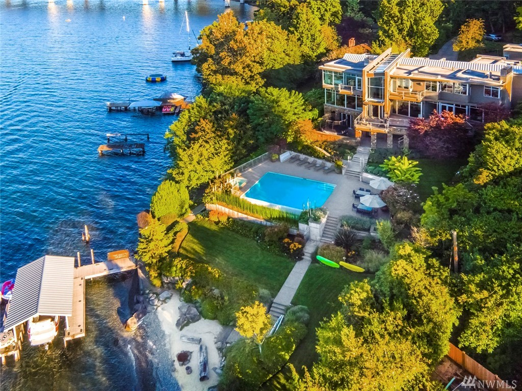 Architecturally iconic waterfront estate on the North End. Walls of windows frame views of the lake creating a backdrop for modern luxury. Formal & casual entertaining spaces abound. Upper level hosts a fabulous view master suite, add'l bedroom suites & office. Endless entertaining on the lower level w/private wine tasting room & gym. Enjoy dinner with friends poolside. Hop in the boat from your private dock or unwind by the firepit on the beach. Magical. Extraordinary. Remarkable in every way!
