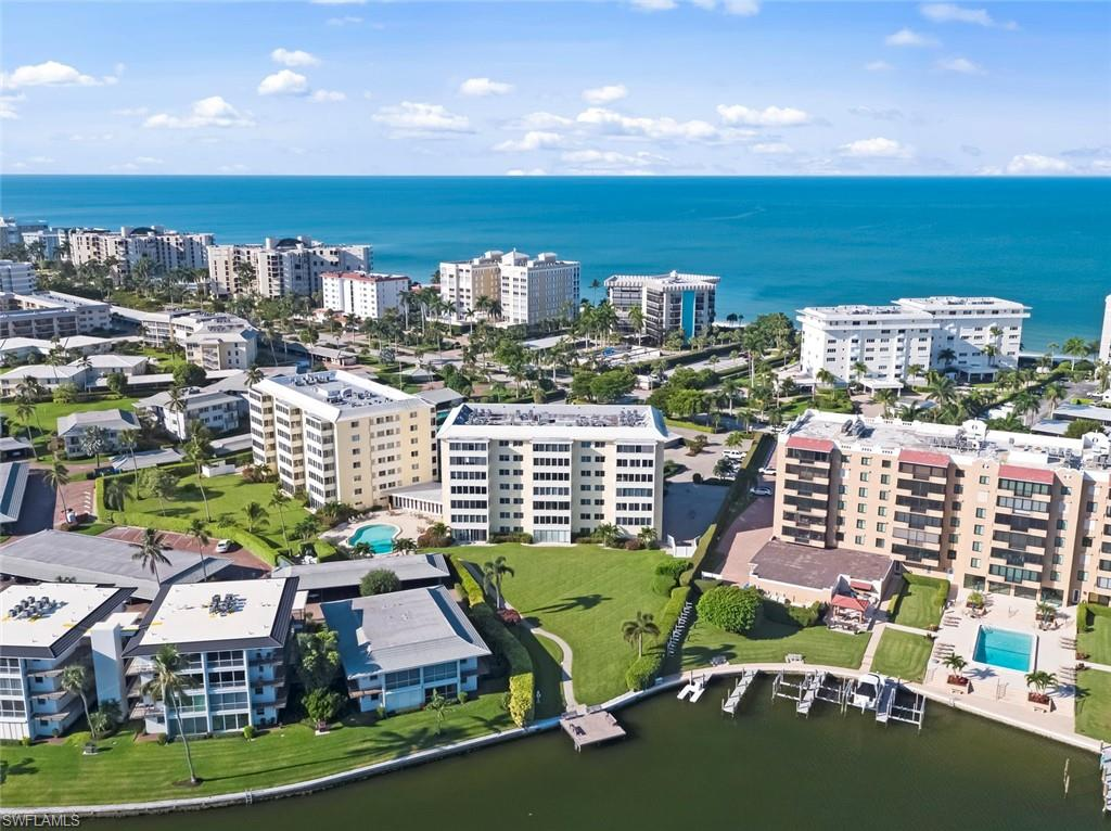 Location! Location! Lo-cation!  This spacious end-unit on prestigious Gulf Shore Boulevard sits across the street from the beach and on Moorings Bay!  The 4th -floor elevation gives you beautiful views of both the Gulf and the Bay! Enjoy your coffee and breakfast at the window overlooking Moorings Bay in the renovated kitchen.  The condo has 2 large bedrooms and 2 full baths, and thanks to new condo rules, the entire condo is able to have hard surface flooring!  The renovated community room, new community boat dock, fitness center, hobby room, beautiful pool with grills, library, vehicle car wash area, bike storage and community wifi are some of the amenities to be enjoyed as well. You can sit on the dock overlooking expansive bay water views or sit on the sandy beach, as you have Beach access directly across the street. This location couldn't be better. Harborside West is just minutes to World renowned 5th Ave, and just a short walk up the street to Venetian Village, both with amazing shopping and dining opportunities. This condo will not be on the market long!