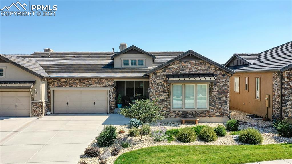 """Meticulously maintained, highly upgraded, maintenance free paired patio home in the desirable Flying Horse neighborhood with views out the front of Pikes Peak. This gorgeous ranch style home w/ walk-out lower level boasts approximately 3,702 FSF with 4 bedrooms and 5 baths plus a main level office. The open and bright floor plan is designed for comfort w/ luxurious finishes throughout. Hickory ebony hardwood flooring in the living room, office, dining area & kitchen. The Chef's kitchen has 42"""" hickory soft close cabinets in slate color & custom backsplash, large center island w/ slab granite, huge breakfast bar, Stainless Steel appliances, gas cooktop & spacious pantry. The dining area walks out to expanded low maintenance deck w/limited golf course views w/ no homes behind. Living room features gas fireplace w/stone surround, ceiling fan & wall of windows. Spacious master suite boasts coffered ceilings, new shiplap wall & opens to the spa like master bath w/ dual sinks, massive shower w/ designer tile, separate water closet & huge walk-in closet. The fully finished lower level has 9' ceilings & opens to covered patio and includes an inviting family room w/ stone surrounded gas fireplace, custom designed media center & a remarkable recreation room w/ huge wet bar equipped w/ wine cooler. All the ingredients for the perfect place to entertain family and guests. There are 2 additional bedrooms & 2 full baths which complete the lower level. 3 Car divided garage & central air conditioning for your convenience. Grounds are well kept featuring mature landscaping w/ all maintenance taken care of by the HOA including the lawn water. With many new upgrades, no details have been overlooked. This home is stunning and a must see! Short walk to the Flying Horse Club House that features dining, spa, fitness and pool."""