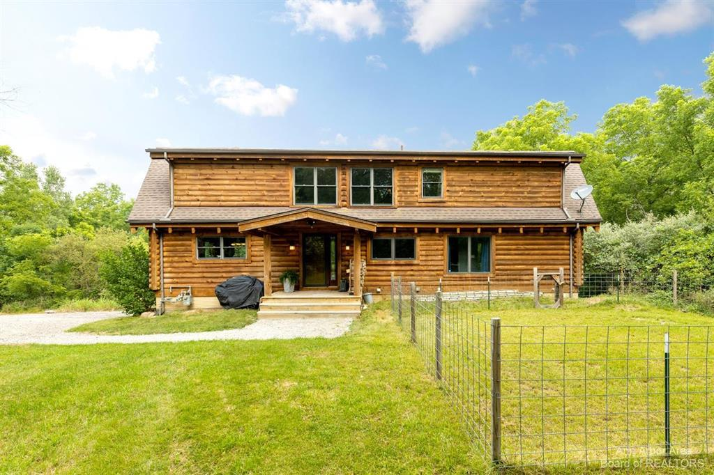 Awesome custom log home with a beautiful, private 2.5 acre lot surrounded by a peaceful wooded landscape, fire pit area, right next to the expanded BTB Trail system and very close to the Huron River. Enjoy sweeping views from your floor to ceiling windows providing sun drenched days and natural light. Step inside and soak in the up north feel with a very open concept floor plan and over 2,600 sq feet of finished living space, including a convenient first floor laundry, generous kitchen/dining area, first floor primary suite, powder room and floor to ceiling stone fireplace for the cozy feeling we all need come winter time. Upstairs you will find an amazing loft/bonus area, a full bath and two large bedrooms. The walk out lower level is partially finished and currently used as a home business but could be easily finished further, making an incredible recreation area for entertaining family and friends. All new carpeting, newly refinished wood floors, fresh interior paint, new roof, new