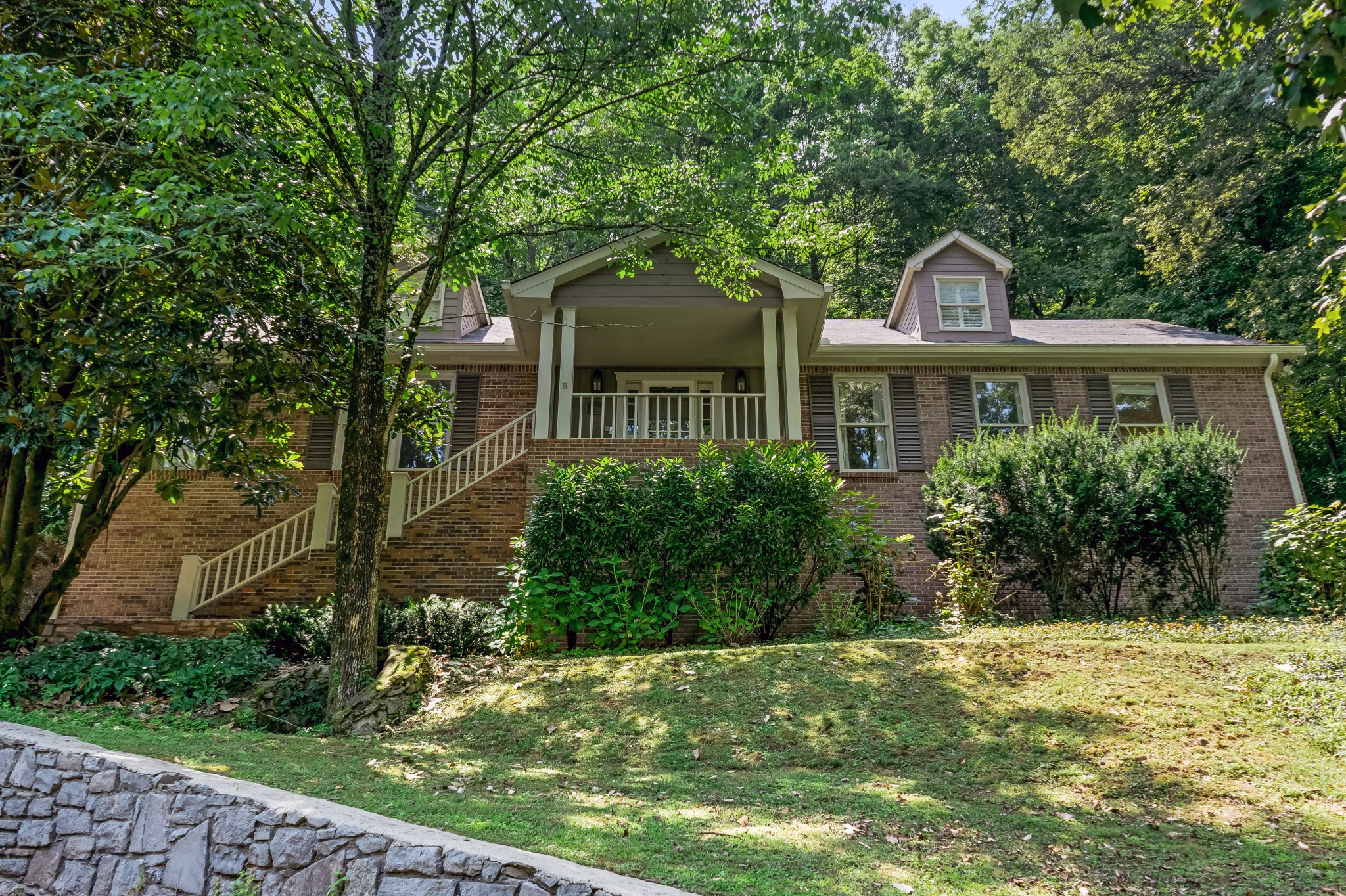 Beautiful hillside home in the heart of Forest Hills! Mature trees on a 1.3-acre lot, walking distance to Radnor Lake State Park. Sprawling floor plan with hardwood floors and beautiful natural light throughout. Five bedrooms with two Primary Bedroom options (fireplace with each). Back patio oasis with fire pit and separate screened-in porch, perfect for indoor/outdoor entertaining. Private location at the end of a quiet, established cul-de-sac. Don't miss this!
