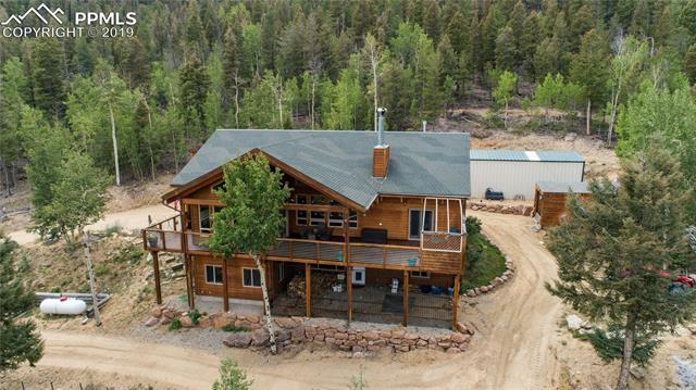 Beautiful mountain retreat nestled against Pike National Forest. Mountain views, open floor plan with knee to ceiling windows and spectacular vaulted ceilings. Kitchen with granite counters, center island, double ovens, gas and electric. Massive rock wood burning fireplace with live edge mantle. Master suite features a new rustic vanity and tile and stone flooring, it is also wired for a gas fireplace.