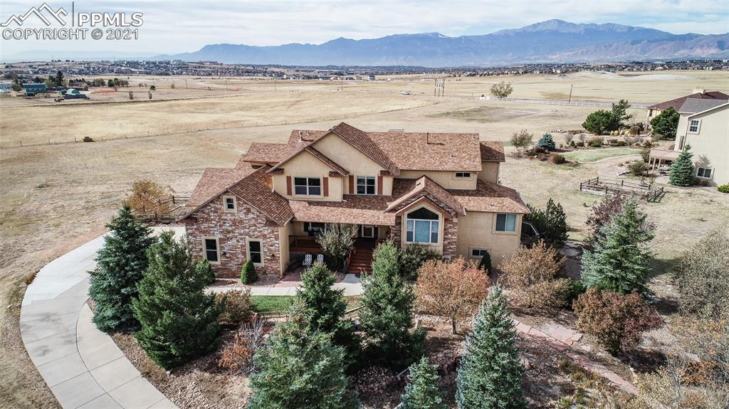 Beautiful family two story w/ main level master & laundry.  Tucked back on 2 1/2 acres with lots of trees & sweeping unobstructed Pikes Peak  & mountain views from the rear including the kitchen, master, both family rooms loft & 2 other bedrooms from all 3 levels - Gourmet island kitchen w/ new slab granite counters w/ tile backsplash, newer stainless black appliances including a gas range w/ disappearing vent, French door fridge, walk in pantry, bayed eating nook & crown molding -