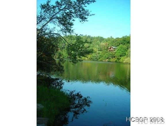 A large estate-sized lake front lot, off-campus to Highlands Country Club and only 5 minutes to downtown Highlands, is special. The lot is a fantastic building site for a large home and guest cottage that gently slopes down to the shore of pristine Lake Sequoyah, providing a serene vista and private lake access for enjoyment. This lot has approximately 460 feet of lake frontage with your privacy assured by a generous lot size. The Property Owners of Lake Sequoyah have a shared private amenity in the exceptional Dock & Pavilion that offers a place to launch and store canoes/kayaks, grill and entertain, or just to relax and enjoy visiting with your neighbors or guests. Boutique downtown Highlands shopping, arts, and restaurants is very close by, yet a world away. Outdoor enthusiasts are also rewarded with canoeing/kayaking, hiking, fly fishing, numerous waterfalls and all that the National Forests and nature that surrounds the area has to offer.