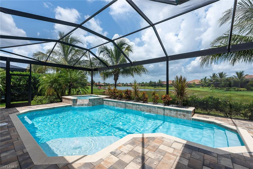 Welcome to this beautiful 3BR + Den lakefront home surrounded by lush landscaping in Lagomar village, in award-winning Fiddler's Creek!  Open Great Room floor plan w/pocket sliders offers access to an oversized lanai with gas-heated pool & spa, summer kitchen with built-in grill, fridge & sink, covered seating area, tanning deck & pool bath. Ample windows, wood-look tile floors in main living areas, coffered & volume ceilings w/crown molding, impact glass, plantation shutters, tankless hot water heater, indoor & outdoor monitored security system, electric remote blinds for sliders. Light, bright kitchen with granite countertops, glass tile backsplash, SS appliances, hood vent, island/breakfast bar, butler's bar with built-in wine rack & wine cooler, walk-in pantry, & dining area, along with a separate dining room for more formal evenings. Master bedroom with lanai access boasts large walk-in closet with built-in closet system, plus en-suite with seamless glass and tile inlay walk-in shower, dual sinks, vanity, linen closet & private WC.  2 more bedrooms with baths for your guests' privacy, laundry with sink & cabinetry for additional storage, spacious den, oversized 3-car garage.