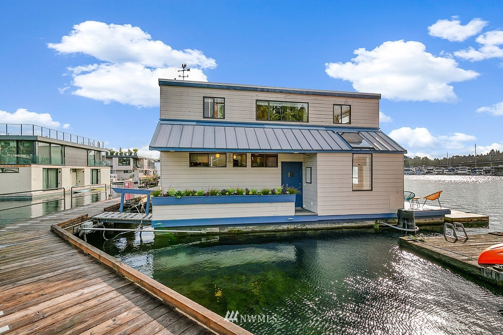 Sun-drenched floating home in sought-after Hamlin Cove. Incredible southern light graces this floating home with big-water views from nearly every window. Built-in bench seating outlines the great room, creating the perfect corner window seat with open-water views on two sides. Warmed by a gas fireplace, the great room, dining, and kitchen enjoy vaulted ceilings and vintage wood-wrapped walls throughout. Efficient kitchen with gas range and breakfast bar. Two additional bedrooms up with enchanting water views and shared 3/4 bath. Delightful outdoor deck off dining room with bonus swim platform. Enjoy an active lifestyle with boat moorage, kayak & SUP storage. Private parking. Cooperative dock ownership in peaceful Portage Bay!