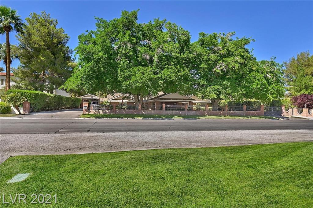 This custom beauty sits on an acre lot, within a historic district, minutes from the Strip and downtown. Electronically gated grounds with a port cochere 2 car entry. 7 -car garages, RV/ 4 car carport. Two separate guest houses, pool, and spa.  The rear yard is breathtaking. It is your very own park setting with a beautiful rose entry gazebo, firepit with guest seating, 2 barbeques, sports court, vegetable garden, Grape arbor, & Pomegranate, Pistachio, Apple, Fig, Lemon, and Pecan trees. The rear yard grounds are an amazing sight to see. The main house boasts a sprawling floor plan with 2 family rooms, + game room, an office.  Beautiful primary suite with fireplace, dual walk-in closets, jetted tub and steam shower, and many rich custom built-ins throughout the home.