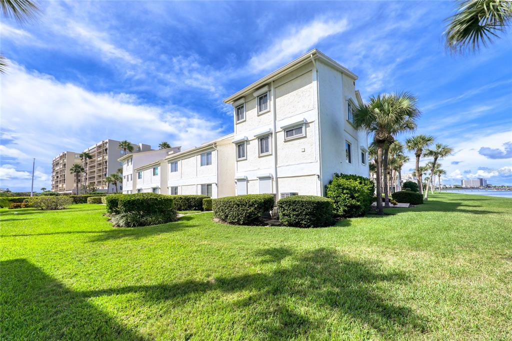 Clearwater Beach at Sand Key.  This corner townhome style condo has wide-open views of the intracoastal and pool. Newer porcelain flooring on stairs, Living room, Dining room and Kitchen. Updates include A/C units in 2018 & 2019, water heater in 2018 & newer sliding doors and windows.  Unit has an open floor plan with breakfast bar. Kitchen features all stainless appliances and new dishwasher.  There's also an inside laundry with full size washer and dryer. Unit is completely remodeled. Upstairs is the master bedroom with two closets and large master bath with double sinks and modern updated shower with seamless shower door. Bedrooms two and three have a continental bathroom shared by both bedrooms. Views from every room. Covered carport parking is included. Enjoy sitting on the balcony and watch the dolphins and wildlife. This is one of the few pet friendly complexes allowing two pets. Beach access directly across the street.  Hurry and make this your piece of paradise!