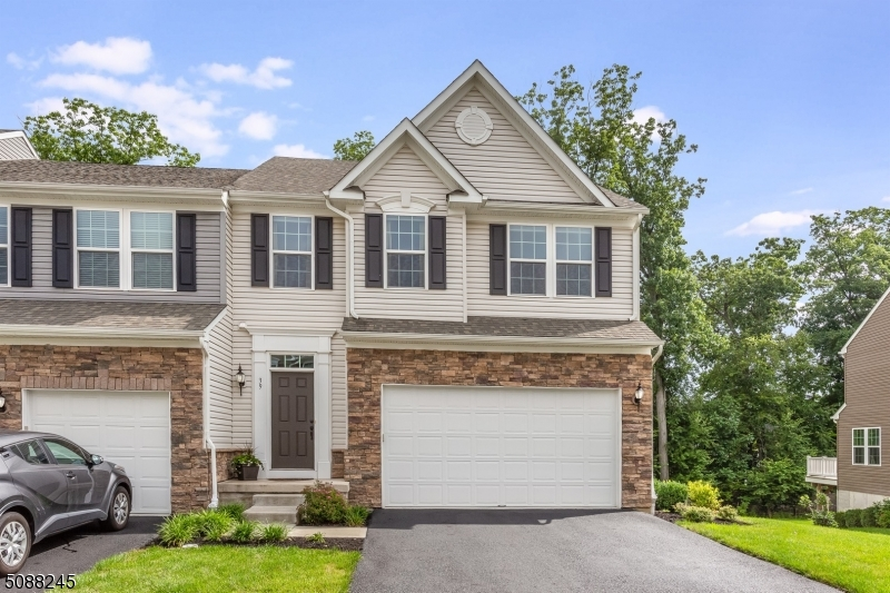 """Just like new! Built in 2017, this beautiful End Unit with a 2 car garage and wooded back view is a rare find. Gorgeous from the moment you walk in, the 5"""" red oak hardwood flooring leads the way to a spacious open concept 1st fl w/ living/dining rm & kitchen. The kitchen is large w/a center island, extended cabinet/counter space. SS appliances, beautiful granite & decorative backsplash. Sliders off the dining area lead to a private deck w/ wooded view. Upstairs offers 3 bedrooms & a reading nook. The master bedroom has a roman shower upgrade & 2 walk-in closets. The basement family rm has sliders to the outside. Add'l storage rm w/full-size window can be another finished rm. Elegant Crown molding & recessed lighting throughout. Mins from rt 80/NJ transit station/Lake Hopatcong. Builders warranty transferable"""