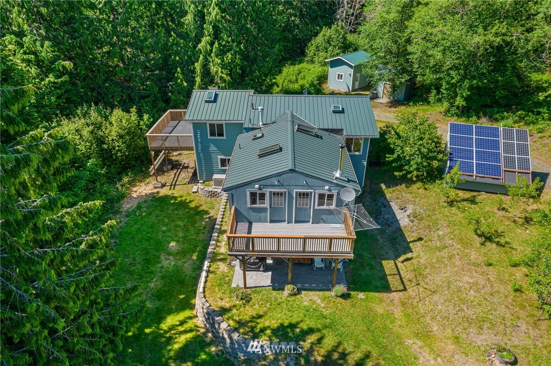 PRICE REDUCED! Fully OFF GRID home on 25 acres borders Nat'l Forest, features creek, powered by solar panels (2020) & generator, radiant heat & Avalon wood stove. Built for those looking to be SELF SUFFICIENT! Spacious tiled kitchen includes propane powered refrigerator, gas cooktop, island, eating area, & woodstove. Master boasts vaulted ceilings, laminate floors, skylight, balcony, walk in closet, dual master shower, and dual sinks (toilets/showers are low flow). Stacked washer & dryer on the upper level stays. Home is septic certified for 2 bedrooms but has 3 plus office and loft. Fenced garden with hoophouse, chicken coop, fruit trees, and outbuildings include tractor storage, pump house, storage & garden sheds. Hi speed internet also!