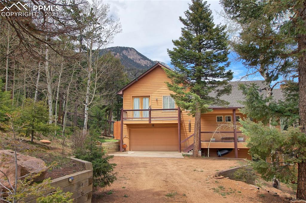 Location, location, location. This stunning custom Palace home located in Upper Crystal Park offers mountain living with easy access to the city. The home boasts views of the Colorado Springs, Cameron Cone, Sunrise Peak, subtle sounds of the waterfall nearby, multiple decks, landscaped yard, vaulted ceilings and large windows throughout to provide tons of natural light. The open layout of the main level allows for easy entertaining or family time. The kitchen is a cook's dream with a double oven, gas cook top, custom countertops/backsplash and a very large breakfast bar. The living room has convenient wet bar, stone fireplace and direct access to the huge wrap around deck. The master bedroom is set apart for privacy, has it's own private deck, adjoining master bath and large walk-in closet. Each of the bedrooms on the lower are large with their own en suite full bathrooms and a walk-out to a deck/patio. Heating of this custom is provide thorugh radiant, in-floor throughout.  The exterior of is designed for outdoor enjoyment! The yard is level, landscaped, has multiple decks and patio area, has a dog run connected to the garage and your very own trail to the four-tiered community waterfall!!! This is a home you will want to tour and not leave!