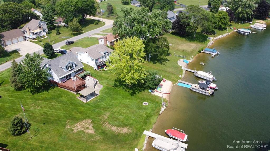 This is your opportunity to own 43ft of water frontage in Irish Hills, Lake Columbia with amazing lake views. All sports, 840 acre private lake. Great for swimming, fishing and docking boats. Massive deck(657sqft) with retractable awning, gazebo(with electricity) and back extensive patio with built in stainless grill, an entertainers dream. Kitchen includes granite counters and gas stove. Inviting living room upon entering, open to kitchen and dining areas, primary bedroom on first floor, full bath on each floor and huge bedrooms.  The walk out lower level includes a large family room with wood burning stove/fireplace and bedroom and bath.  Two car garage that has a full attic with built in ladder, lake fed sprinkler system.  Amazing space for a big family and/or plenty of guests. Dock included. Lake Association includes many annual activities and 4th of July fireworks, 11 public parks with full restrooms and playscapes. Lots of Michigan wineries to explore. Taxes and association fee l
