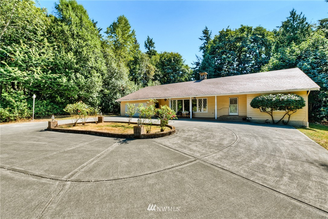 Located on over half an acre, this gorgeous mid-century modern home offers ultimate privacy & a rare opportunity to be outside of the city with easy commutes. Grand entry with roundabout driveway & endless possibilities w/extra space. Bright & open living with a grand room, soaring ceilings, formal dining, & stunning fireplace. Impressive main suite w/oversized jetted tub. Newer energy efficient heating/cooling system & renovated bathroom, laundry, & mudroom.