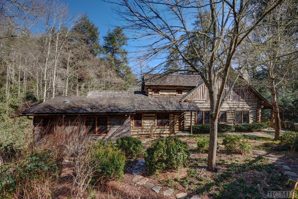 Vintage logs, a cedar shake roof, expansive rear covered porch looking out on your own private dock and canoe launch.  The Cullasaja River is the rear boundary of this property. It is fairly calm so the conveyed canoes can immerse you in nature. This home and its environment are simply beautiful. Tom Chambers built this exceptional, mini-estate to evoke the ambiance of a hunting lodge. It is constructed of recycled logs, with oak and chestnut interior surfaces, although relatively new, it appears very old. Owners have brightened the interior with additional windows, and skylights, encapsulated the basement and enclosed a basement room to provide a heated workshop and storage. Three additional, recently acquired undeveloped lots provide a buffer along the east side. Totaling about 2.76 acres, Fishtales is private, yet very close to the vibrant activities of Highlands. Catch trout off your dock, and enjoy leisurely meals on the expansive covered porch overlooking the water. (Porch photos are waiting for spring.) Three wood burning fireplaces: in the living room, den and on the covered rear porch, take the nip out of the air on cool summer nights. Rustic luxury!