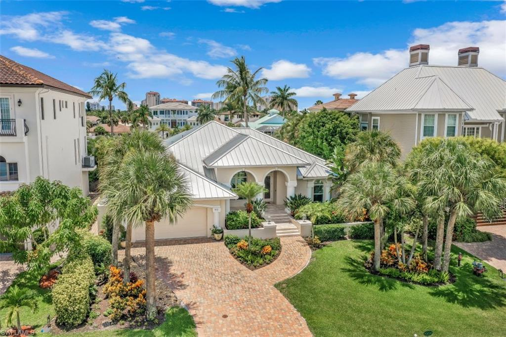 Charming Southern exposure updated ranch-style home! This coastal, light, and bright home is move-in ready and offered TURNKEY! The great room floor plan works perfectly for for entertaining.  A few key points not to be missed: Cambria polished quartz counters, high-end stainless appliances (Thermador induction stovetop, Decor Subzero refrigerator), with custom cabinetry and lighting. Legno Bastone oak hardwood floors, app-controlled AC and pool system, impact windows and doors, butane fireplace, Lutron lighting control, new exterior paint, landscape lighting, AND metal roof (2014).  The garage is also outfitted with tile flooring for easy clean-up.  The gorgeous outdoor patio has natural stone that walks out to the oversized dock and boat lift that has a 13k lb lift (2019).  Mercato, Whole Foods Market, Trader Joe's, and gorgeous beaches are just a mile away!