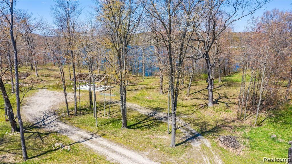 Build your dream estate on over 400' of frontage on prestigious, All Sports Spring Lake! Just under 14 acres of beautiful lakefront property with it's own stream. 1 mile off I-75, and Holly Schools, this land is a rare opportunity. This is also a builders dream. Potentially build 3 estate homes on this property, or own your own slice of 'Up-North' Heaven!