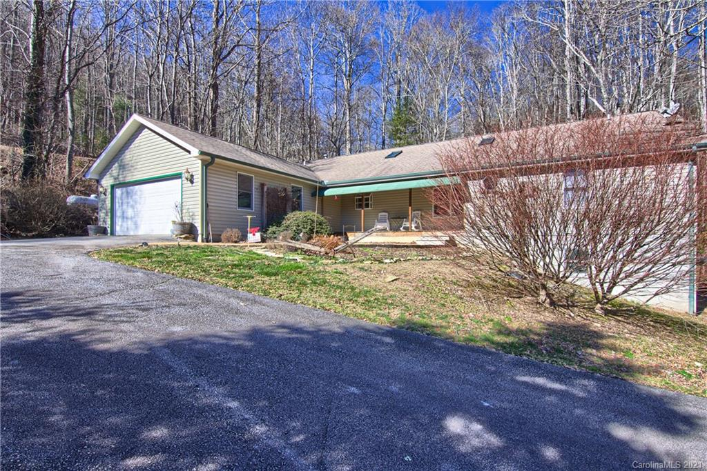 Come see this quiet mountain retreat on 5.5 acres without the long drive and steep roads.  Beautiful natural waterfall cascading through the back year with a huge screened porch overlooking it to enjoy it.  Large spacious rooms with an open concept floor plan make this easy living for everyone.  Underground utilities stay out of sight while you enjoy your uninterrupted view of nature.  With 5,326 square feet of space there is a workshop as well as a two car garage so plenty of room for every hobby.  The old barn on the property has beautiful wood that could be sold to the vintage enthusiasts or over haul for your own mini farm. SELLER IS OFFERING A HOME WARRANTY.