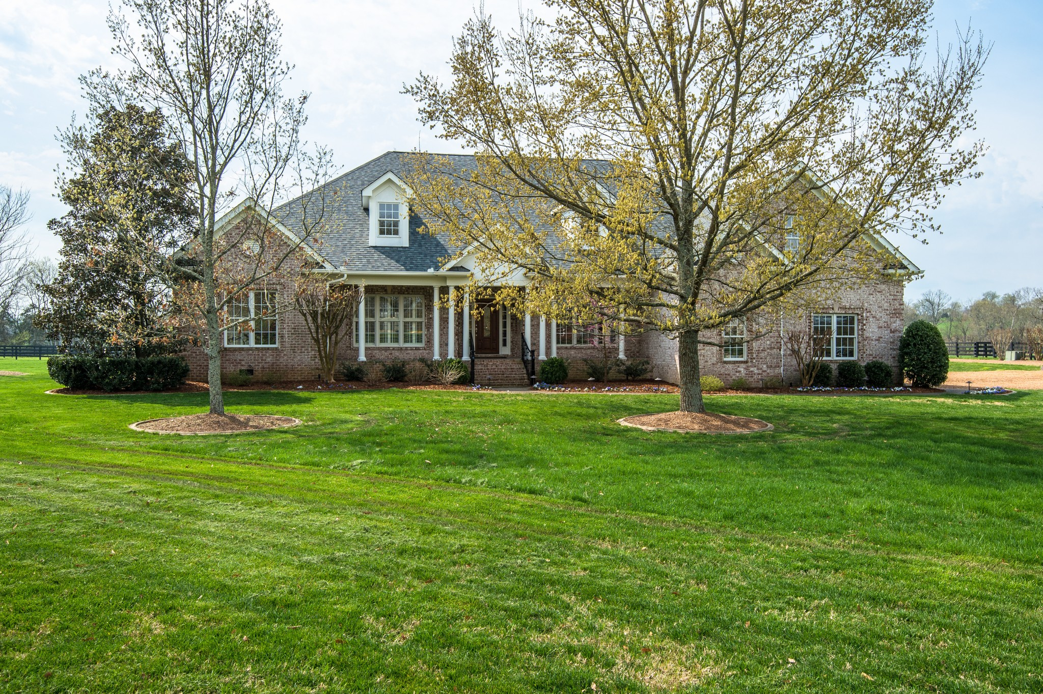 Fabulous,gated,quality custom brick on 23+ level fenced/cross-fenced acres mins from !65,840 and Cool Springs.Offering a 4-stall Morton barn w/heated & cooled half bath, water heater, utility connections plus heated/cooled workshop/mancave/partyroom House has new Int/ext paint, new roof,a stunning 28x20 screen porch,gourmet granite kitchen w/Thermador gas range,glistening hardwoods throughout.Expansive Mstr w/deep trey ceiling & crown moldings,9' ceilings,storm shelter,solar panels & more!