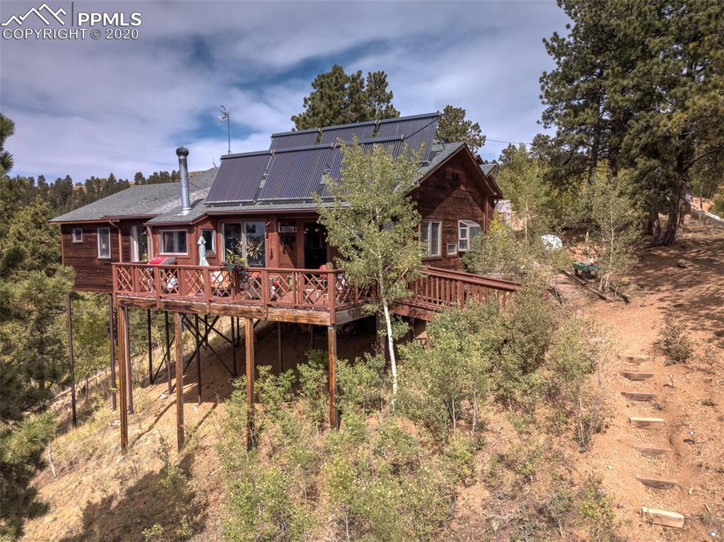 AMAZING BREATHTAKING VIEWS, YOU ARE ON TOP OF THE WORLD, ENJOY COFFEE ON YOUR DECK TAKING IN ALL THE BEAUTY THIS HOME HAS TO OFFER.  NEARBY PRIVATE ENTRANCE TO RAMPART RANGE AND ALL THE NATIONAL FOREST HIKING YOU CAN IMAGINE.  SUPER OPEN FLOOR PLAN WITH OUTSTANDING GREAT ROOM, MOUNTAIN STYLE BAR, ALL OPEN TO KITCHEN & DINING ROOM.  KITCHEN HAS A SPACIOUS PANTRY, JUST AS YOU ENTER FROM THE GARAGE.  KITCHEN OFFERS THE CHEF IN YOU A GAS STOVE W/ DOUBLE OVEN, MICROWAVE/CONVECTION OVEN, REFRIGERATOR AND DISHWASHER, ALL STAINLESS STEEL APPLIANCES.  2 BEDROOM, 2 BATH, 2 CAR GARAGE.  ALSO YOU'LL ENJOY THE HOT WATER RADIANT HEAT, SUPER SOLAR PANELS, PASSIVE SOLAR, WOOD STOVE, WALKOUT TO YOUR DECK AND ENJOY DINNER THERE TOO.  ENTER IN THRU THE FROSTED DOORS TO YOUR BEAUTIFUL OVERSIZED MASTER BEDROOM, WITH ROMANCTIC TUB & CHANDELIER, WALKIN CLOSET, PRIVATE BATHROOM AREA FOR YOUR SHOWER, WASHER & DRYER.   THE SUNSETS WILL BE AMAZING, YOU WILL NEVER WANT TO LEAVE, IT'S THAT AMAZING!