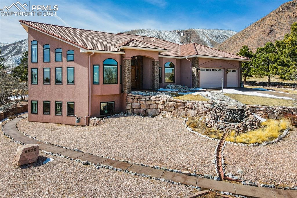 Welcome home to this highly appointed custom home nestled in the heart of desirable Mountain Shadows with both city and mountain views! Super private and quiet location on a .6 acre lot backing to open space. Minutes from Garden of the Gods, Ute Valley Park and other trails for hiking and biking. D-11 and D-20 schools are both close by, choice into either one. This rancher has true main level living and is wheelchair friendly with zero-grade entries at the front door and garage. An elevator gives additional access to all floors. Custom features are built into every room. 18' ceilings, gorgeous Wisconsin oak floors, and Pella Windows greet you as you step through the door into the great room. A grand staircase and open loft area give you an amazing retreat to take in the views for miles!  The gourmet kitchen features gorgeous granite, high-end appliances, wall ovens, induction range, upgraded Schroll cabinets with soft-close drawers, roll-out pot racks and mixer stand, a huge walk-in pantry as well as a butler's pantry. The main level master has a cozy fireplace, sitting area and walk-out to the deck. The light and bright master bathroom features a large soaking tub, dual vanity and a walk-in closet. An inviting staircase takes you to the lower level where you will find a huge family room, large kitchenette, and two additional bedrooms and bathrooms. A large office with built-ins has its own private exterior access that could be perfect for a home-based business or even home schooling. Many outdoor areas are available for entertaining including the covered patios and decks that run the length of the house. The large and private lot is fully landscaped with mature trees, a pond and two water features, and large grassy areas with an underground watering system. The flower beds and garden areas contain many spring bulbs and other seasonal plants throughout the summer. This is definitely a home that you need to see in person to appreciate all its amenities and features.