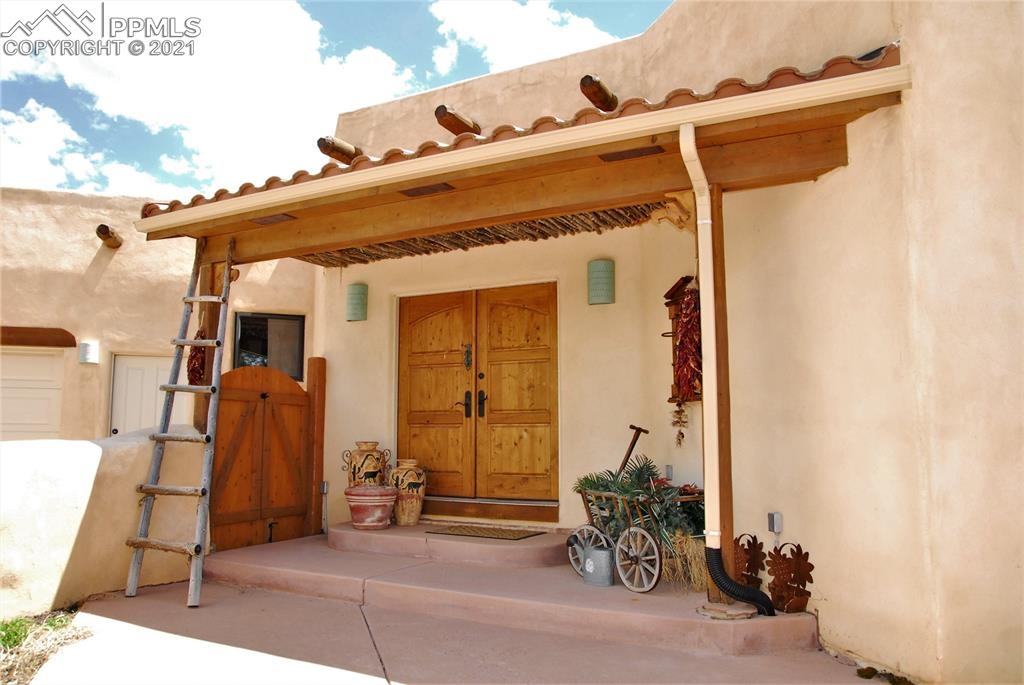 Great private & secluded location, yet very close to a bustling mountain town! Custom Santa Fe-style rancher on 4.27 gorgeous acres with stunning Pikes Peak views! Generous-sized Great Room has open beam ceilings and Kiva gas fireplace that provide the charming ambiance. Saltillo terra-cotta tile throughout most of the expansive main level. Fabulous southern exposure, skylights, and abundant windows makes everything light and bright, and ensures you'll stay toasty warm all winter.  Very spacious Kitchen features oversized island, breakfast bar, solid granite countertops, stainless appliances, and custom pecan cabinetry. At the end of the day, retreat to the Huge Master bedroom with its gorgeous view of Pikes Peak, private access to the patio, hardwood floors, walk-in closet, and 5-pc bath with jetted tub and doorless walk-in shower! 3 spacious secondary bedrooms also on the main level; two share Jack-and-Jill Full Bath with private sinks & commodes; the third has adjoining Full Bath. 4 of the 5 bedrooms have private walk-out access to the covered wood decks or patios. Walk-out lower level includes a Family Room that is perfect for home schooling, home office, hobbies, home gym, etc. Another bedroom, full bath, & storage room complete the lower level. Unwind in front of the outdoor Kiva or hot tub as you take in the natural beauty all around. Currently an artist studio, the detached 'Casita' has been used as a barn and attached garage/stall is perfectly sized for a tractor. Loafing shed and fenced corral are ready for your horses...zoned A-1 with a DOMESTIC well! Surrounded by horse farms and forest for enhanced privacy & seclusion. Very well-maintained and updated. New rubber membrane roof in 2020, leach field and radon installed 2016. Paved driveway has lots of southern exposure ensuring snow melts quickly. The full list of features is simply too long to describe here. Come see for yourself everything this unique home has to offer...it's even better in person!