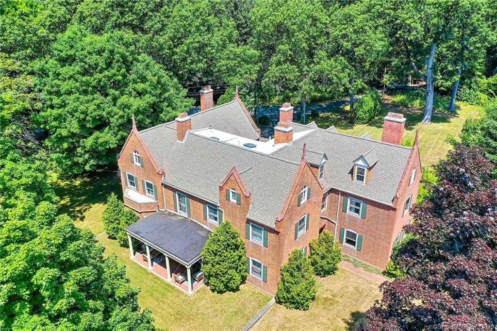 The distinguished Howell Cheney Mansion is a rarely available grand estate located on over two sprawling acres in the Cheney Brothers National Historic Landmark District. Surrounded by mature trees this private estate overlooks the Great Lawn, is mere steps from Labyrinth Brewing Company, and only a short walk to Main Street's shopping and dining. This nearly 7,000 square-foot brick Colonial was completed in 1901 and has hosted such distinguished guests as President William Howard Taft and American poet Robert Frost. Nearly every room on all three levels of the mansion features expressive historic details such as handcrafted woodwork, built-ins, original moldings, and wood floors. The home has been fully restored and impeccably maintained, and the owner has done a superb job of maintaining the home's historic details while modernizing the electrical, plumbing, heating, roof, and more. The first floor features a spectacular front-to-back grand foyer, formal living room with a brick fireplace and built-ins, a fully remodeled chef's kitchen with center island, honed granite counters, subway style backsplash, stainless steel appliances including a commercial grade gas oven/range and a large butler's pantry, a formal dining room with a brick fireplace and an incredible built-in hiding a Prohibition-era secret compartment, sitting room, billiards room with a brick fireplace and a dedicated first-floor laundry room. The master suite occupies nearly the entire west wing of the home featuring sleeping quarters with a brick fireplace, a newly renovated master bath, and a large walk-in closet with built-ins. The expansive second floor also includes three additional bedrooms all with fireplaces and built-ins, two additional full baths, and two flex rooms perfect for a second-floor office, library, or playroom. The finished third floor has a separate entrance and includes an eat-in kitchen, sitting room, three (or four) bedrooms, and two full baths (one is roughed in).